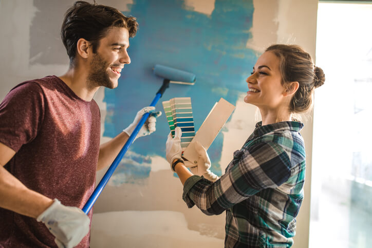 Couple Painting The Walls Together